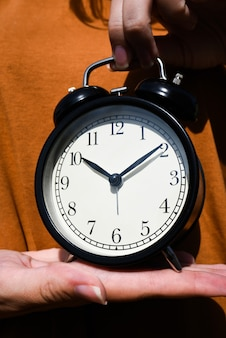 Женщина в коричневой футболке, держа в руке будильник. концепция потерянного времени. бизнес-идея. стиль жизни