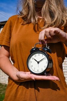 目覚まし時計を手に持っている茶色のtシャツの女性。失われた時間の概念。ビジネスアイデア。ライフスタイル