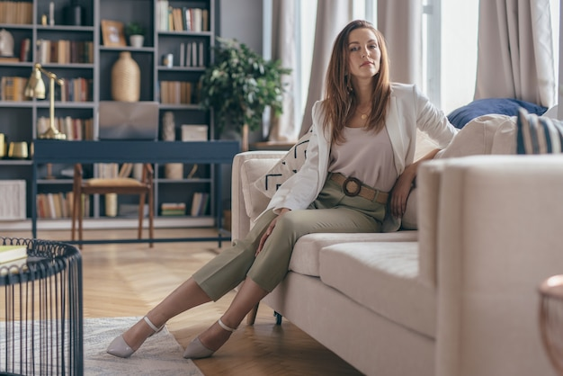 소파에 쉬고 집에서 퇴근 후 비즈니스 복장에 여자.