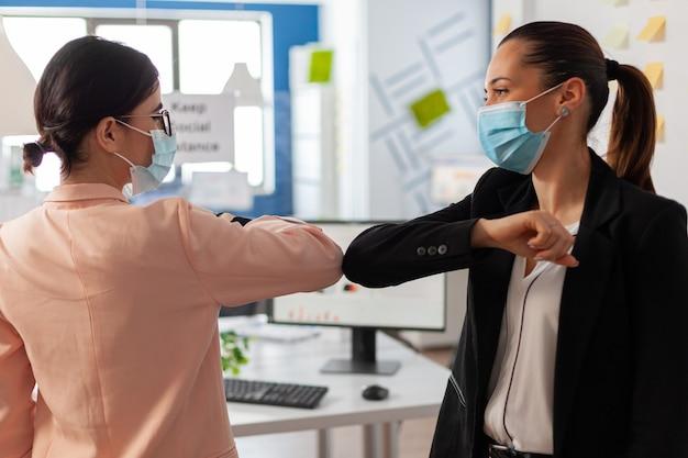 코비드19 독감으로 전 세계적으로 유행하는 동안 얼굴 마스크를 쓰고 팔꿈치를 만지는 안전 예방 조치를 따르는 비즈니스 사무실의 여성. 서로 인사하는 동료들.
