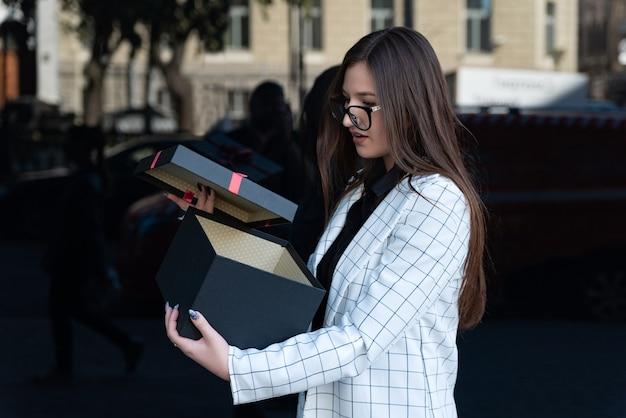 Женщина в деловом костюме и очках с удивлением открывает подарок. красивая женщина раскрыла черную подарочную коробку.