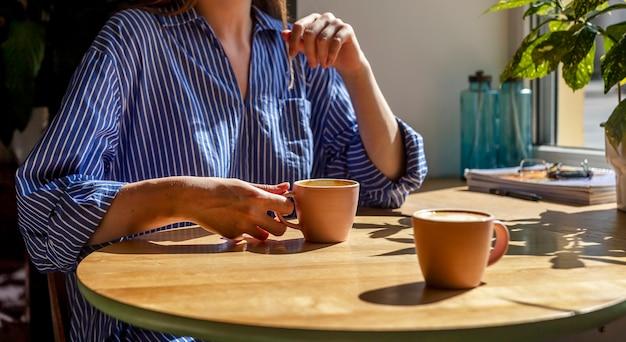 Женщина в кафе на встрече с кем-л. с чашкой кофе за современным деревянным столом с растениями и солнечным светом