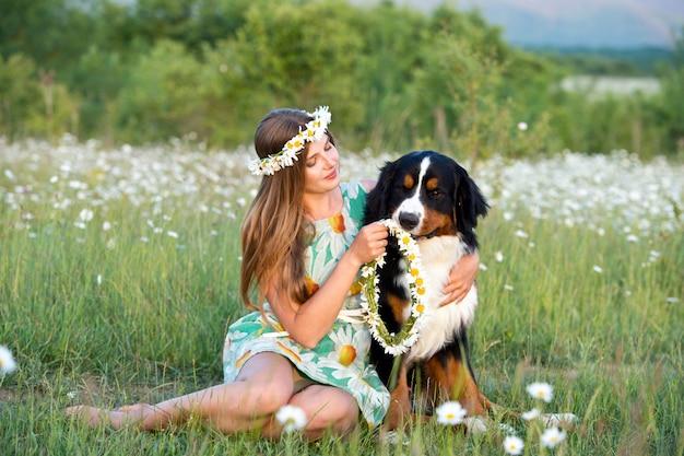 バーニーズマウンテンドッグとカモミールリースの女性。犬を持つ少女