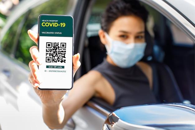 Женщина в машине показывает экран смартфона с вакциной в паспорте с covid-19 или коронавирусом и знаком qr-кода, чтобы показать, что она уже получила вакцину. концепция коллективного иммунитета.