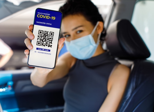 Женщина в машине в маске показывает экран смартфона с вакцинацией в паспорте с коронавирусом или паспортом здоровья и знаком qr-кода, чтобы показать, что она уже получила вакцину. концепция коллективного иммунитета.