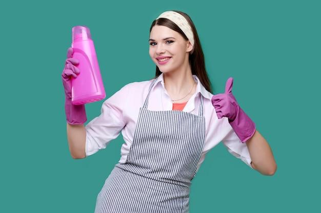 Женщина в повседневной одежде и резиновых перчатках держит чистящие средства