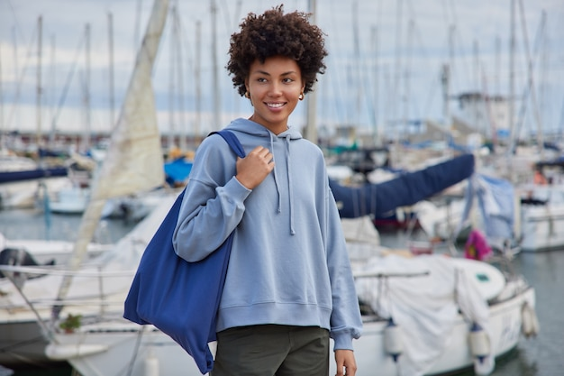 カジュアルな服を着た女性が布製のバッグを運び、桟橋の港を散歩します。新鮮な海の空気がボートを待っています。