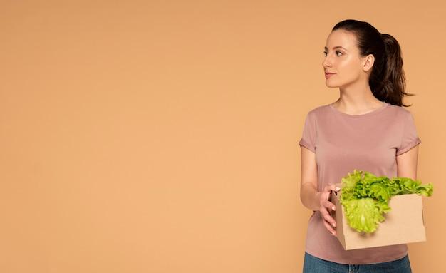 Женщина в повседневной одежде, несущая многоразовую мультяшную коробку с овощами