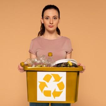 Женщина в повседневной одежде, несущая многоразовую коробку для переработки