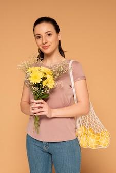 Женщина в повседневной одежде, несущая многоразовую сумку-черепаху и цветы