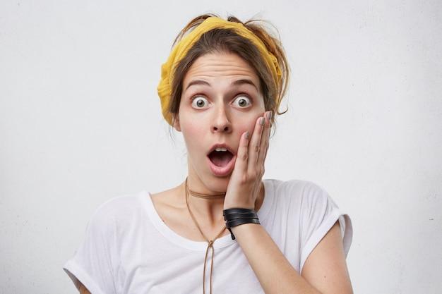 カジュアルな服を着た女性が頬に手を伸ばして頬を手にしてショックを受けて口を開けた