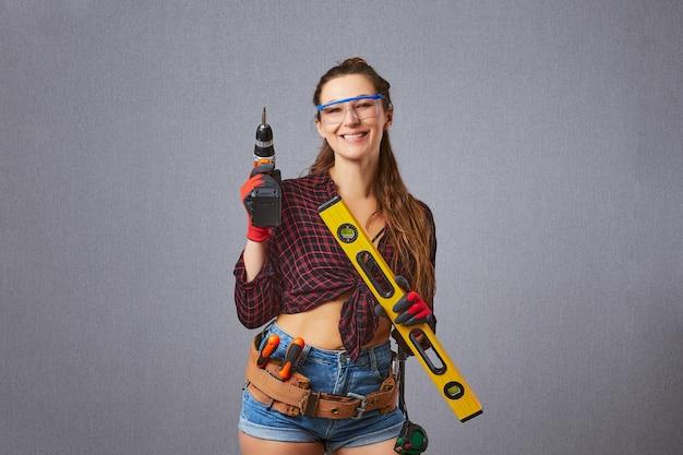 평상복 보호 장갑을 낀 여성이 전기 드릴이나 드라이버 수리 홈 개념을 들고 있습니다.