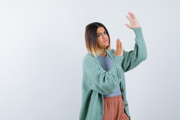 Женщина в повседневной одежде показывает жест отбивной каратэ и выглядит уверенно, вид спереди.
