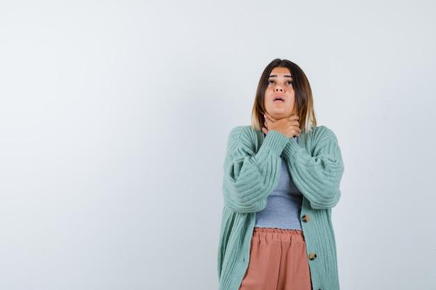 喉の痛みと病気に苦しんでいるカジュアルな服装の女性、正面図。