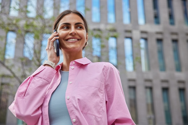 カジュアルな服装の女性がスマートフォンを使って会話をしているモダンな建物の近くの通りに立って目をそらしている都会の環境を楽しく歩き、ガジェットで余暇を楽しんでいます