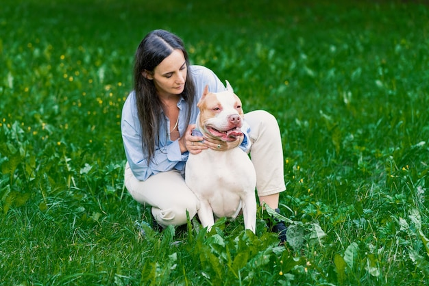 Женщина в повседневной ласке американского питбультерьера на траве счастливая собака с высунутым языком, оглядываясь вокруг