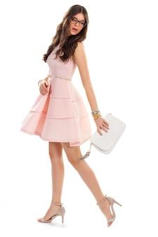 캐주얼 연어 드레스에 여자입니다. 안경에 예쁜 여자입니다. 힐 슈즈와 짧은 드레스. 액세서리가 있는 여름 파티 복장.