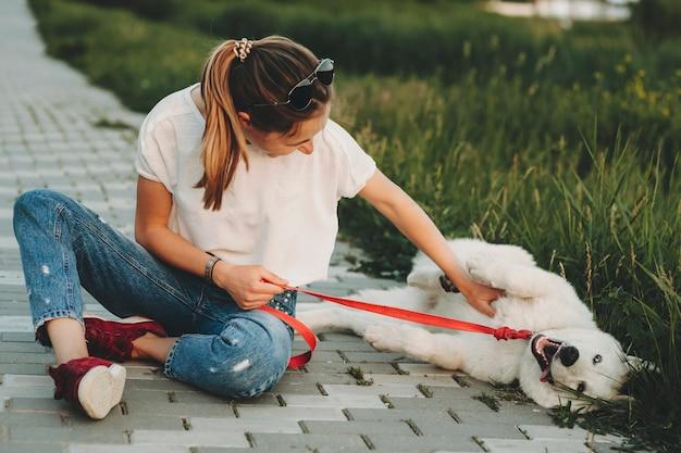 公園の舗装に座って、口を開けて近くに横たわっているふわふわの白い犬の腹を掻くカジュアルな夏服の女性