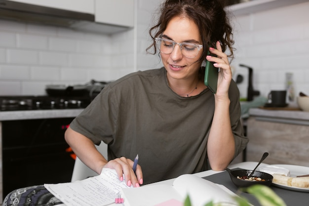 朝食をとりながら、紙の仕事をし、キッチンで電話で話すカジュアルなtシャツの女性