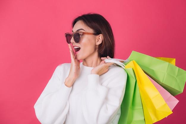 Женщина в повседневном белом свитере и солнцезащитных очках на красной стене