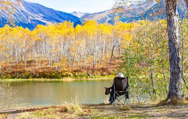 キャンプのための椅子の女性