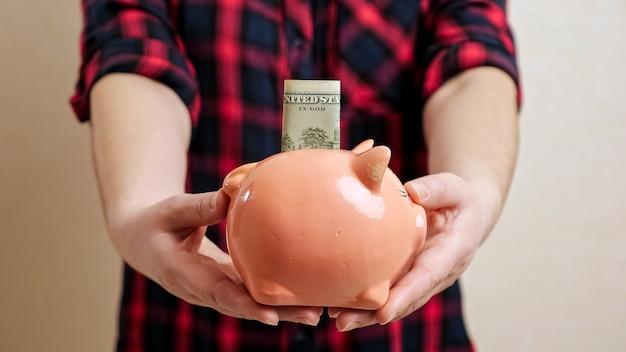 체크 무늬 셔츠를 입은 여성은 슬롯 계획 가족 예산 근접 촬영에서 튀어나온 달러 지폐와 함께 작은 둥근 돼지 저금통을 들고 슬림 팔을 확장