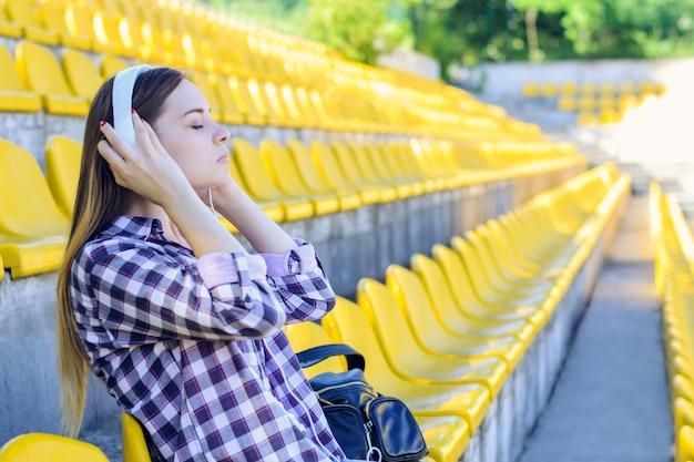 Женщина в клетчатой рубашке в наушниках, сидя на стадионе