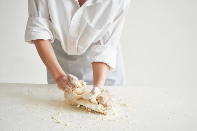 キッチンでシェフの制服を着た女性が生地調理食品ベーカリーを展開します。高品質の写真 Premium写真