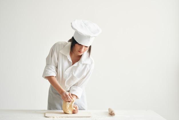 キッチンで制服を着たシェフの女性が生地調理食品ベーカリーを展開