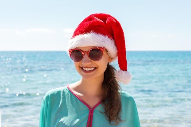 해변에서 크리스마스 모자에있는 여자