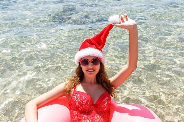 Женщина в новогодней шапке с розовым кругом, расслабляясь в синем море.