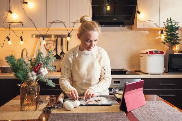 크리스마스 스웨터를 입은 여성은 디지털 태블릿의 조리법에 따라 부엌에서 진저브레드 쿠키를 요리하기 위해 곰팡이로 반죽을 잘라냅니다.