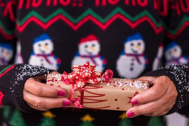 白い雪をまぶした再生紙で贈り物を提供するクリスマスセーターを保持している女性