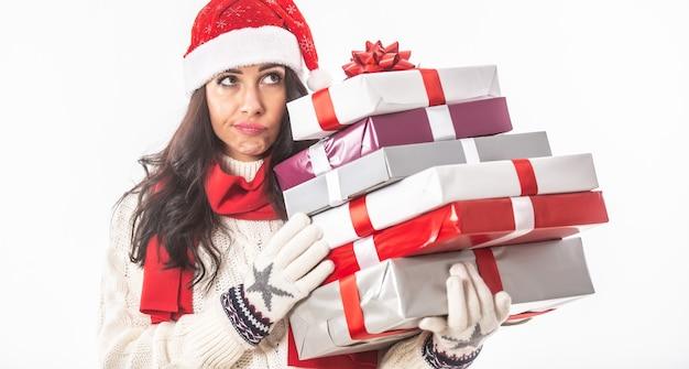 Женщина в одежде рождества держит стопку упакованных подарков, думая о том, что она забыла.