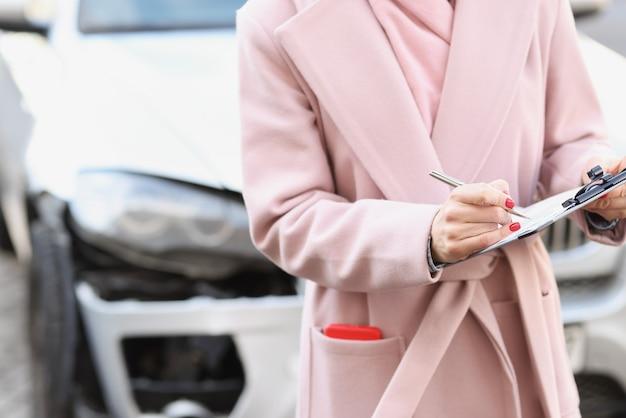 부서진 자동차 근접 촬영의 배경에 대해 문서를 작성하는 코트를 입은 여자. 자동차 보험 개념