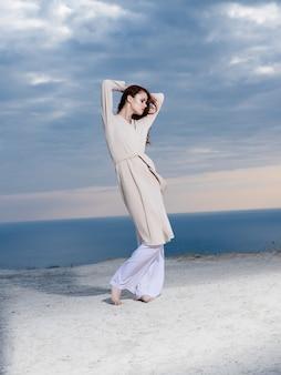 海の夏の風景をポーズするコートの魅力の女性