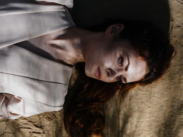 Женщина в пальто лежит на песке летнего образа жизни