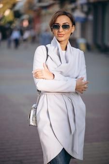 通りの外側のコートの女性