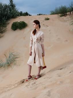 コートの女性ポーズビーチ新鮮な空気モデル旅行。高品質の写真