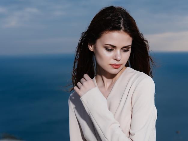 ビーチの風景海の新鮮な空気のポーズをとるコートの女性