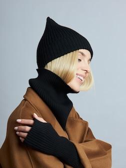 코트, 봄 옷, 스누드 스카프, 모자와 장갑에 여자. 소녀는 파란 눈을 가진 금발입니다. 추운 봄 날씨에 따뜻한 옷