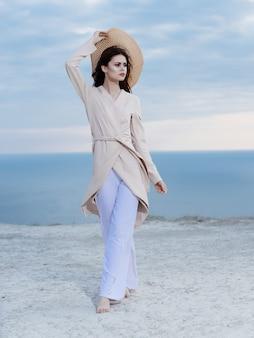 コートを着た女性がモダ島のポーズをとってビーチの海に沿って歩く