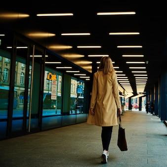 코트를 입은 여성이 가방을 들고 도시 거리를 걷다