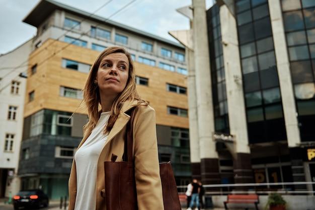 Женщина в пальто идет по улице города