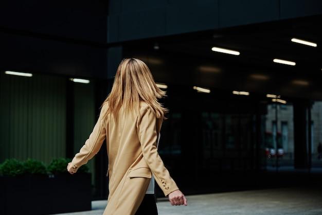 코트를 입은 여성이 도시 거리를 걷다