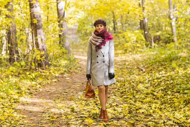 가 공원에 서있는 갈색 가방 코트에 여자