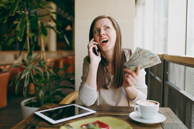 ドル、現金、携帯電話、カプチーノのカップ、ケーキ、自由時間中にレストランでリラックスしてテーブルでコーヒーショップの女性。 pcタブレットコンピューターで働く女性はカフェで休む。