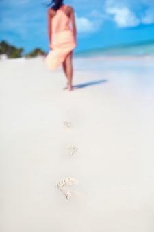 Женщина в красочном платье гуляет по берегу океана, оставляя следы на песке