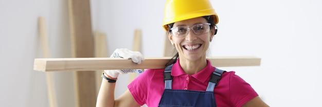Женщина в строительном шлеме и комбинезоне, держа деревянную доску на плече в мастерской. концепция столярных работ