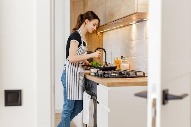 Женщина в приготовлении здоровой пищи на домашней кухне концепция досуга домохозяйки домашнего образа жизни